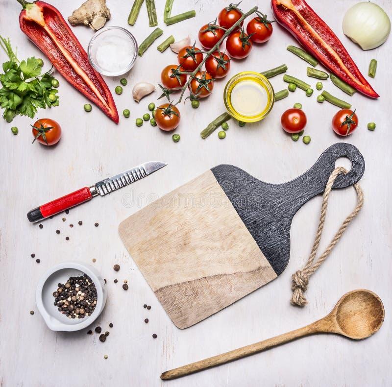 Konzept der guten Nahrung, des verschiedenen Gemüses, der Gewürze und des Öls mit einem Schneidebrett, des Gemüses eines Messers  stockfotos