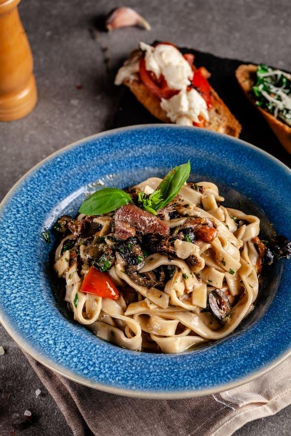 Konzept der italienischen K?che Teigwaren mit Sardellen, Meeresfrüchte und Gemüse, Oliven, Tomaten und Basilikum Servierteller lizenzfreies stockbild
