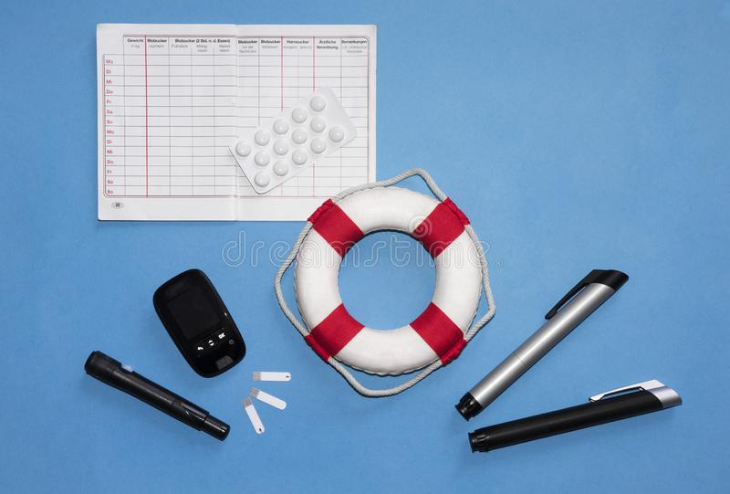 Konzept der lebensrettenden Geräte eines Diabetikers: Messgerät, lancing Gerät, Teststreifen, Tagebuch in der deutschen Sprache,  stockfoto