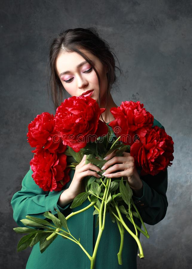 Konzept der Leute und der internationalen Frauen Tages- glückliche asiatische junge Frau mit Bündel Pfingstrosenblumen über graue stockfotos