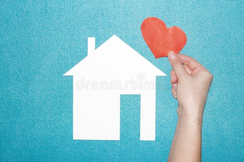Konzept der Liebe in der Familie und zu Hause Hand hält rotes Herz über Weißbuchhaus auf blauem Hintergrund Versicherung des Grun lizenzfreie stockfotografie