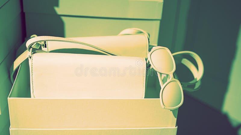 Konzept der modischen weiblichen Zusatztaschensonnenbrille auf leeren Kästen und grünem rosa Hintergrund lizenzfreie stockbilder