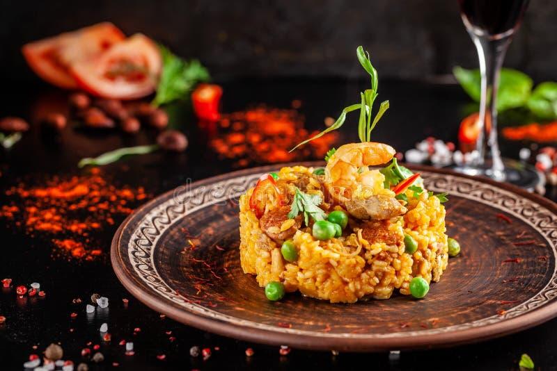 Konzept der spanischen Küche Paella mit Meeresfrüchten und Garnelen, mit grünen Erbsen in einer Lehmplatte Ein Glas kühler Wein i lizenzfreie stockbilder