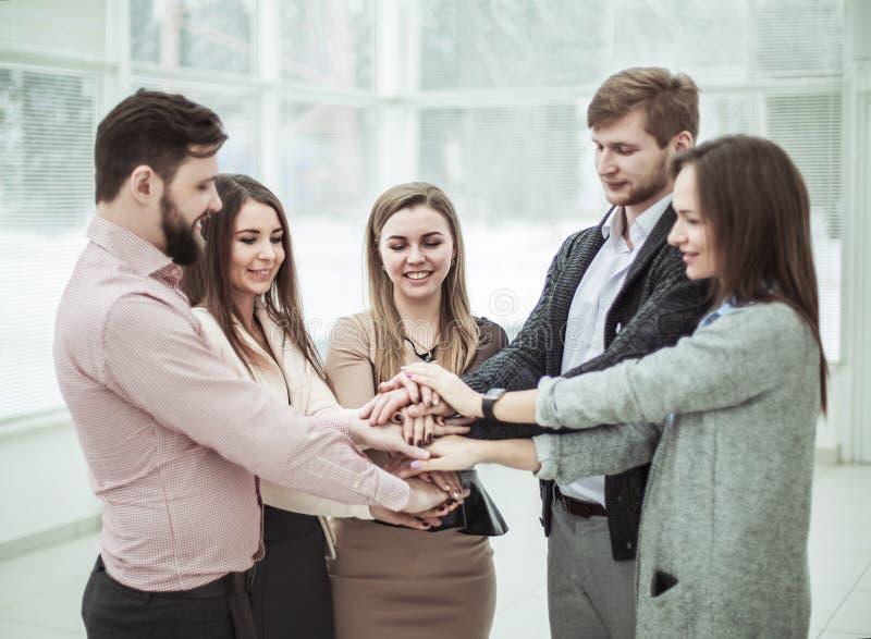 Konzept der Teamwork: freundliches Geschäftsteam, das in einem Kreis, Hände zusammen umklammert steht stockbilder