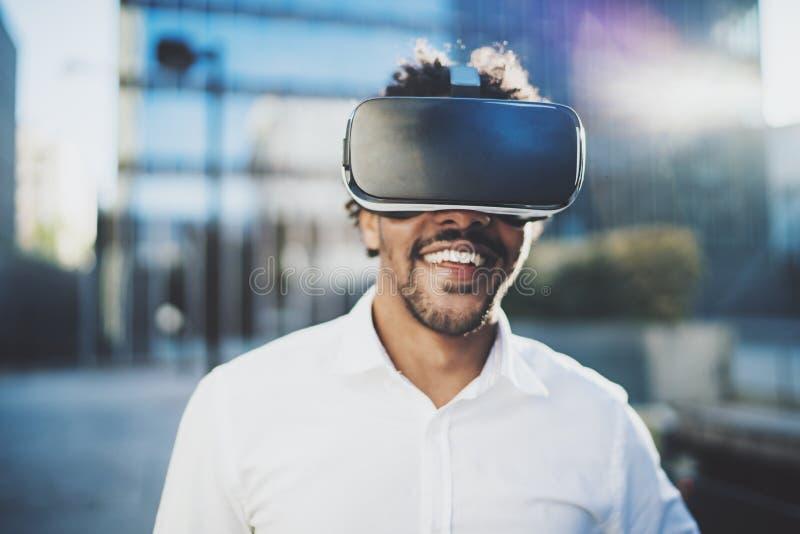 Konzept der Technologie, des Spiels, der Unterhaltung und der jungen Leute Lächelnder amerikanischer afrikanischer Mann, der virt stockfotos