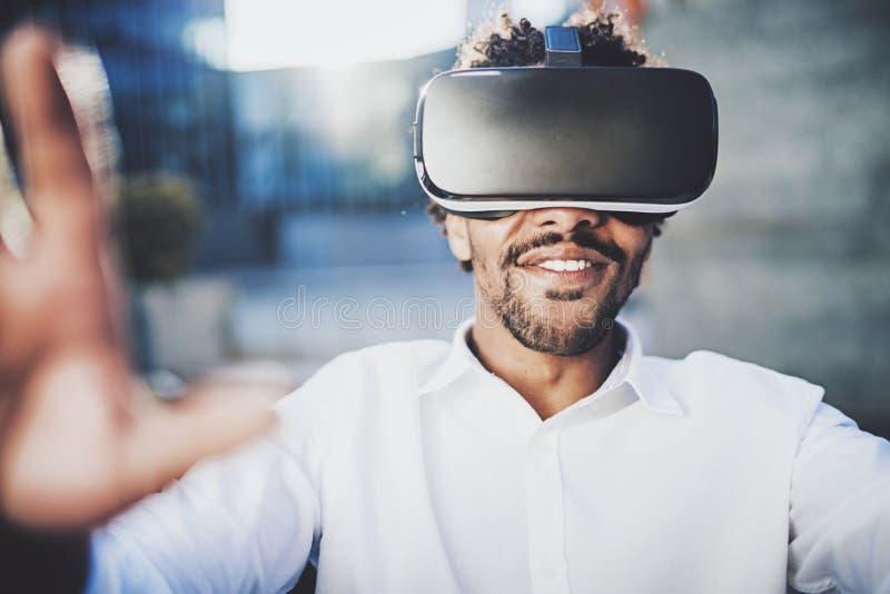 Konzept der Technologie, des Spiels, der Unterhaltung und der jungen Leute Lächelnder amerikanischer afrikanischer Mann, der virt stockfotografie