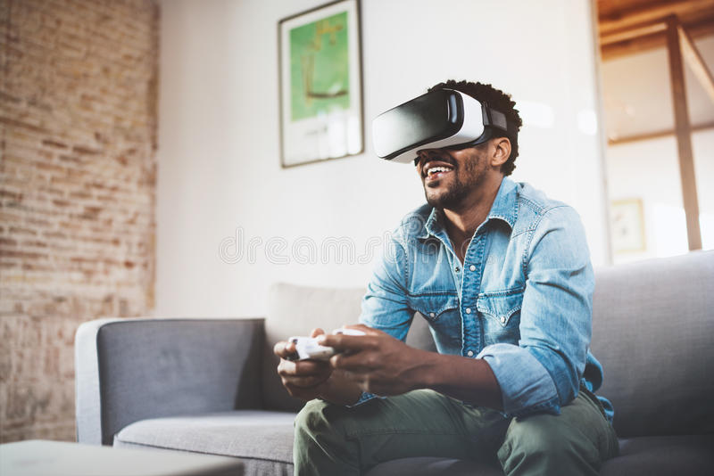 Konzept der Technologie, des Spiels, der Unterhaltung und der Leute Glücklicher afrikanischer Mann, der Gläser der virtuellen Rea stockbilder