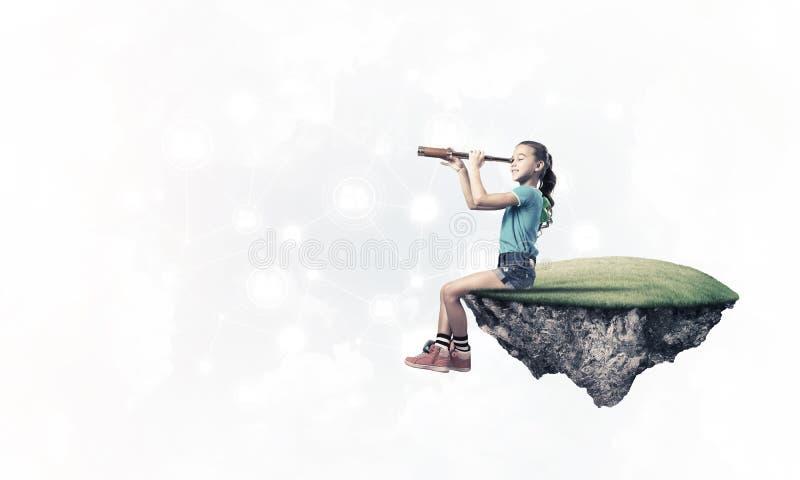 Konzept der unvorsichtigen glücklichen Kindheit mit dem Mädchen, das in den spyglas schaut stockfotografie
