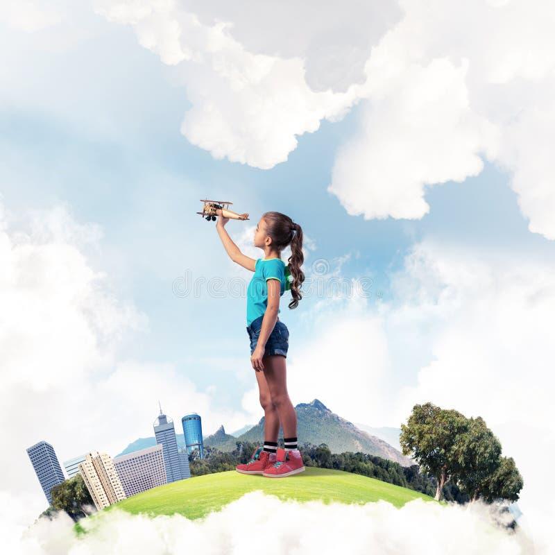 Konzept der unvorsichtigen glücklichen Kindheit mit dem Mädchen, das träumt, um zu werden stockfotografie