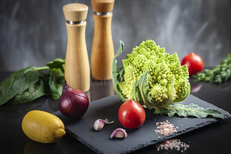 Konzept des biologischen Lebensmittels mit Frischgemüse: Romanesco-Brokkoli, reife Tomaten, rote Zwiebel lizenzfreies stockfoto