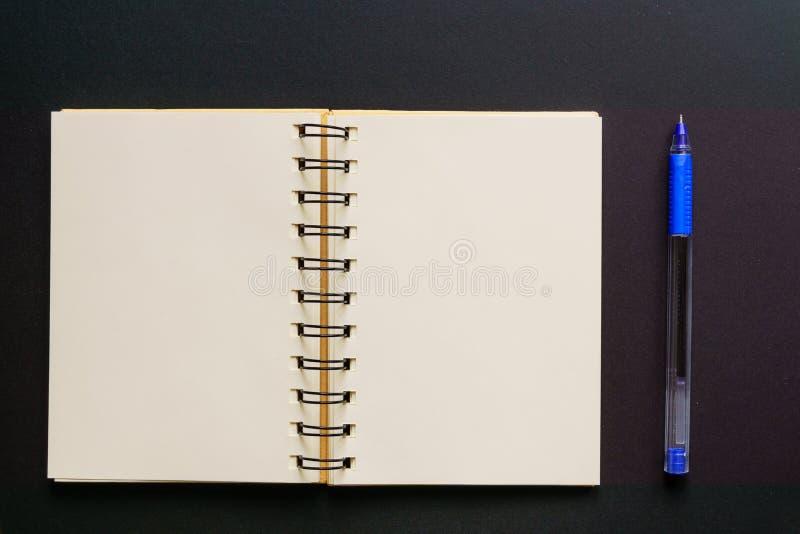 Konzept des Entwurfes - Draufsicht leeren Kraftpapier-Notizbuches und des blauen Kugelschreibers auf schwarzem Hintergrund Spott  stockfoto