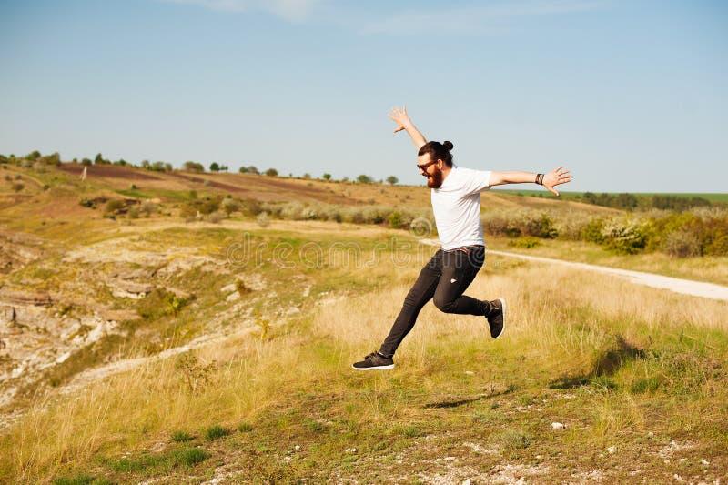 Konzept des Erfolgs draußen feiern - der moderne Mann des Spaßes, der mit den Armen springt, hob mit Energie für Sieg und Glück a stockfoto