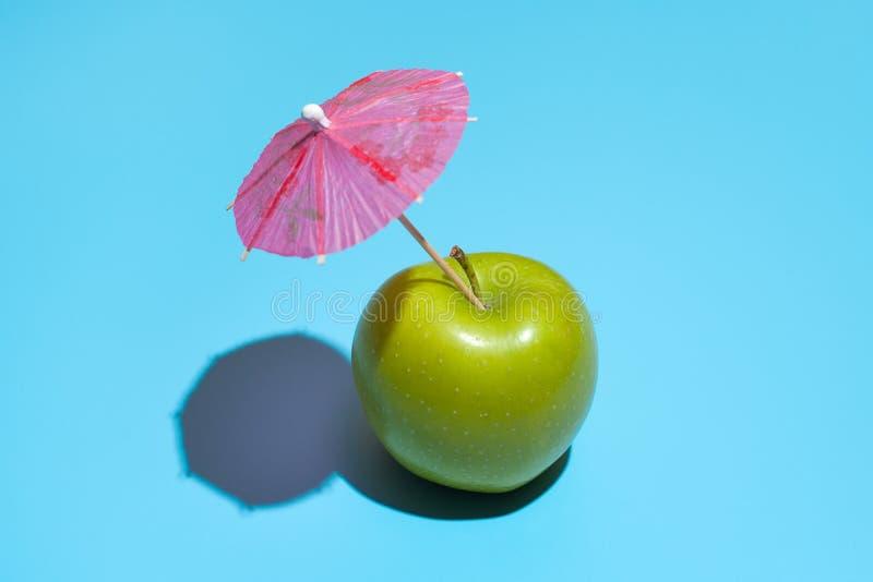 Konzept des frischen grünen Apfels mit einem Regenschirm lokalisiert auf blauem Hintergrund stockfotografie