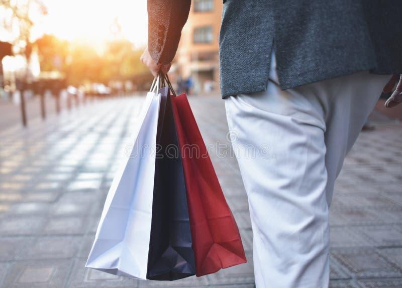 Konzept des Manneinkaufens und der halten Taschen, Nahaufnahmebilder Schließen Sie oben von den Papiereinkaufstaschen in der männ stockfoto