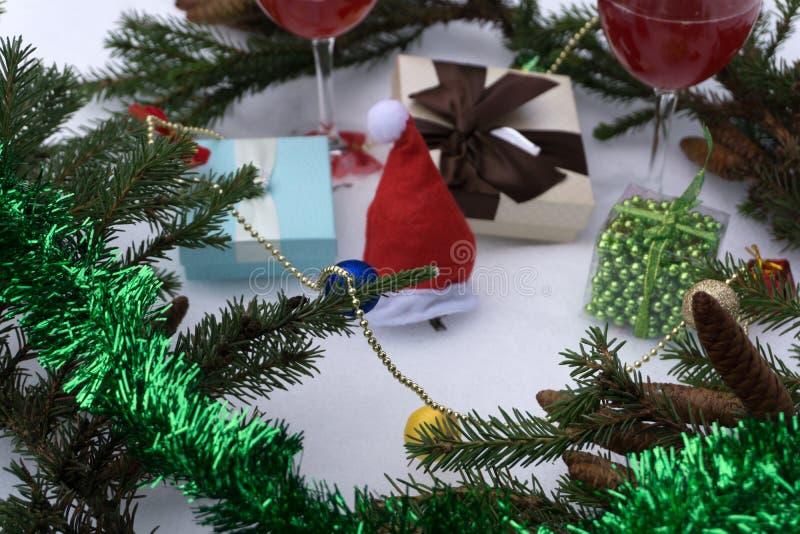 Konzept des neuen Jahres mit den schneebedeckten Kiefernblättern, bunt und zwei Gläsern Wein auf weißem Hintergrund stockbild