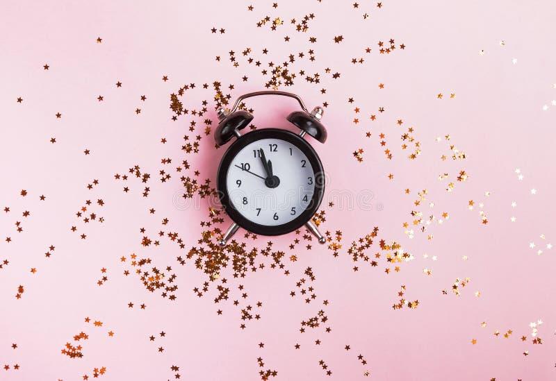Konzept des neuen Jahres oder des Weihnachten mit der Uhr, die herum zwölf P.M. und Gold sternförmige Konfettis zeigt stockfoto