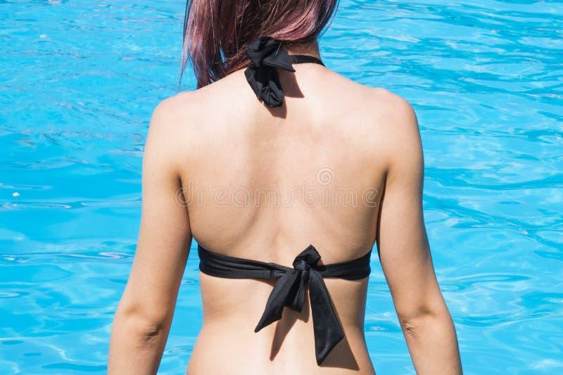 Konzept des sicheren Sonnenbades Kopierraum Nackt von einer jungen Frau gegen das blaue Wasser am Pool Leerraum für lizenzfreies stockbild