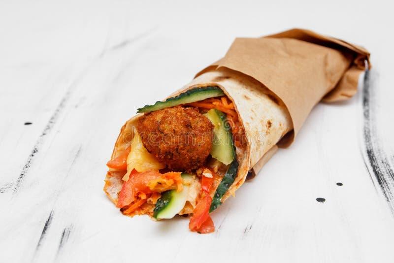 Konzept des vegetarischen Lebensmittels Köstliche frische selbst gemachte vegetarische Tortilla mit Falafel auf einem hölzernen K lizenzfreie stockbilder