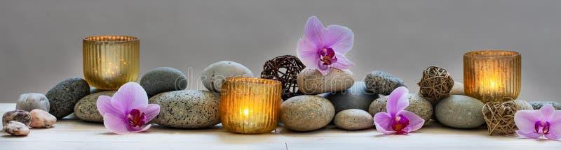 Konzept des Wohls mit Kieseln, Orchideen und Kerzen, panoramisch lizenzfreie stockbilder