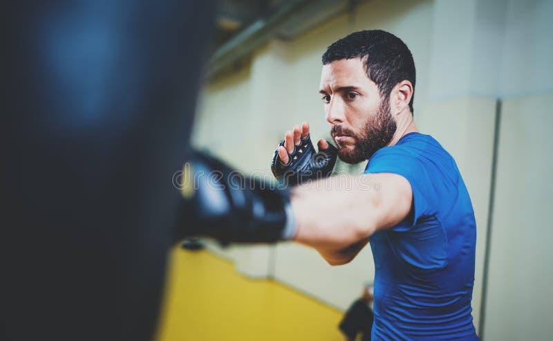 Konzept eines gesunden Lebensstils Übende Tritte des bärtigen muskulösen Mannkämpfers mit dem Lochen der schwarzen Tasche Trittbo stockbild