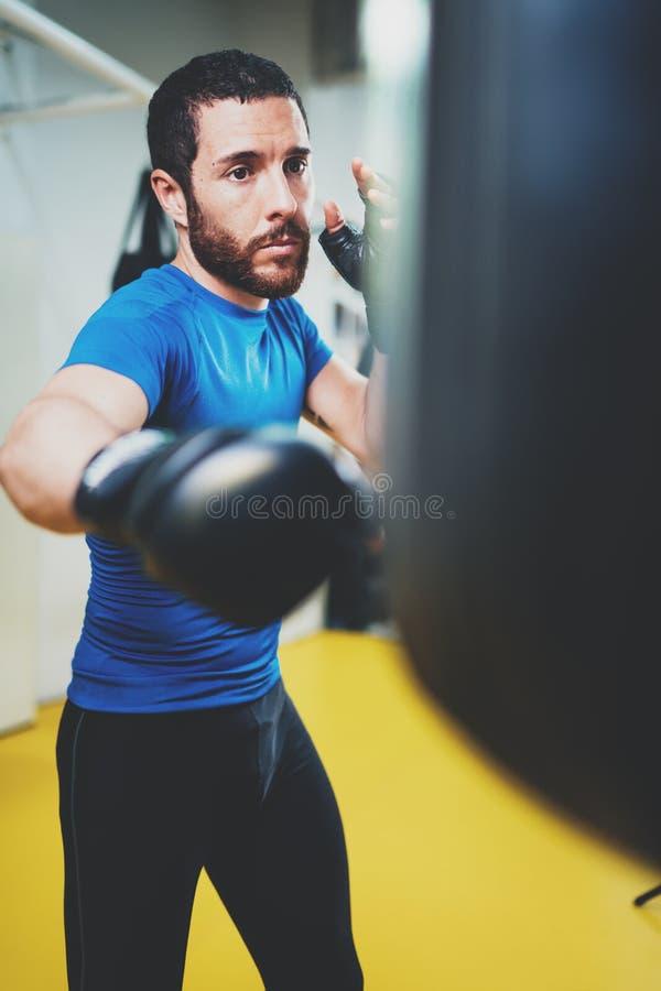 Konzept eines gesunden Lebensstils Übende Tritte des jungen Athletenkämpfers mit Sandsack Trittboxerverpacken als Übung stockfoto