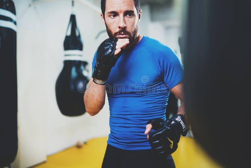 Konzept eines gesunden Lebensstils Übende Tritte des jungen muskulösen Mannkämpfers mit dem Lochen der schwarzen Tasche Trittboxe stockfotos