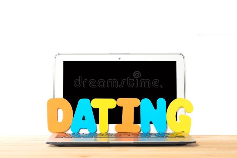 Konzept für on-line-Internet-Datierung Moderner Laptop mit der Datierung der Arbeit von den bunten Buchstaben gegen weißen lokali stockfotografie