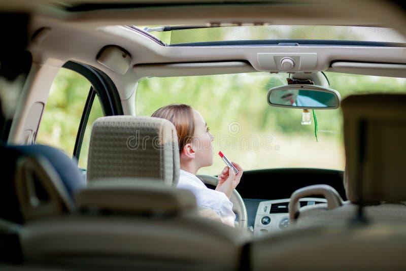 Konzept Gefahrendes fahrens Die rote behaarte Jugendliche des Fahrers der jungen Frau, die ihre Lippen tun das Zutreffen malt, bi lizenzfreies stockbild
