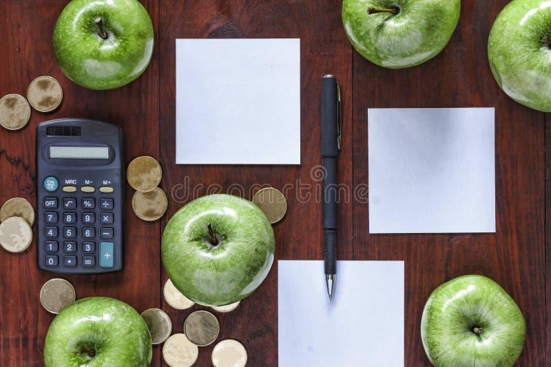 Konzept: Geschäft, Investition, Bereicherung, Logistik, planend Grüne Äpfel, Goldmünzen, Taschenrechner und Papier für Eintritte  stockfoto