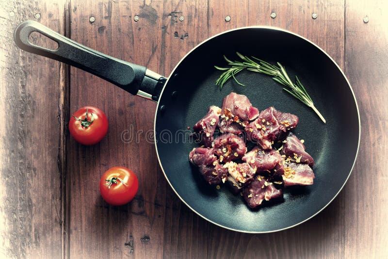 Konzept: Hausmannskost Rohes Gulaschrindfleisch in einer Bratpfanne mit Rosmarin und Gewürzen stockfoto
