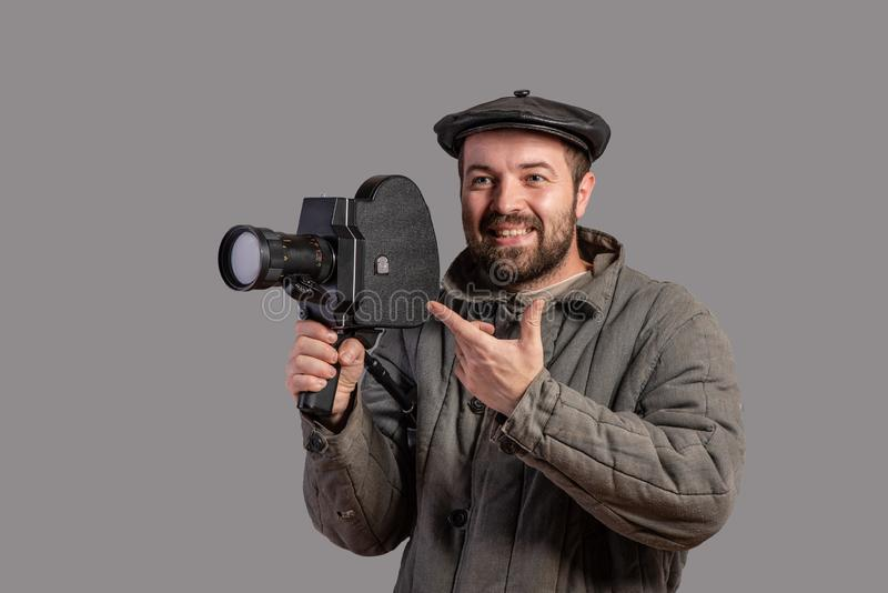 Konzept - lächeln Sie bitte Emotionaler Kameramann mit Retro- Kamera in seinen Händen, Atelieraufnahme Altmodische Kleidungsart F stockbilder