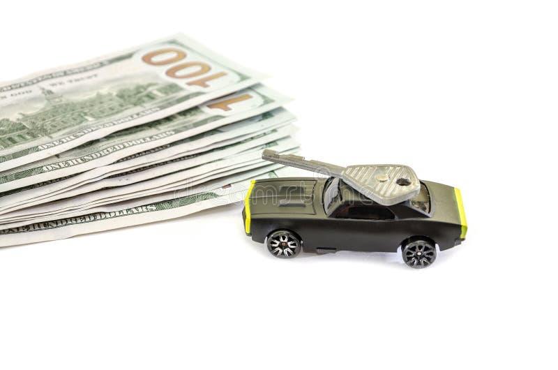 Konzept mit den Dollar, Spielzeugauto und Schlüssel lokalisiert auf weißem Hintergrund stockfotografie