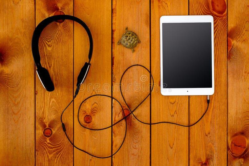 Konzept mit Tablette und schwarzen Kopfhörern auf hölzernem Hintergrund lizenzfreie stockfotografie