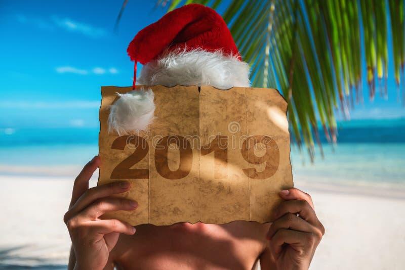 Konzept 2019 Touristischer Mann mit Santa Claus-Hut, der auf tropi sich entspannt stockbilder