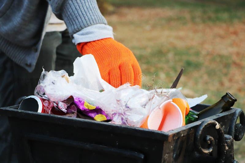 Konzept von Ökologie und Schutz des Planeten vor Rückstand Freiwilliger säubert Abfall im Park und wirft ihn im Abfalleimer lizenzfreies stockfoto