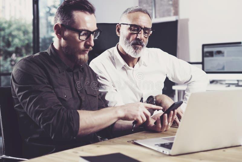 Konzept von den Geschäftsleuten, die Prozess treffen Bärtiger junger Mann, der Handy verwendet Erwachsener Kollege, der zusammen  lizenzfreie stockbilder