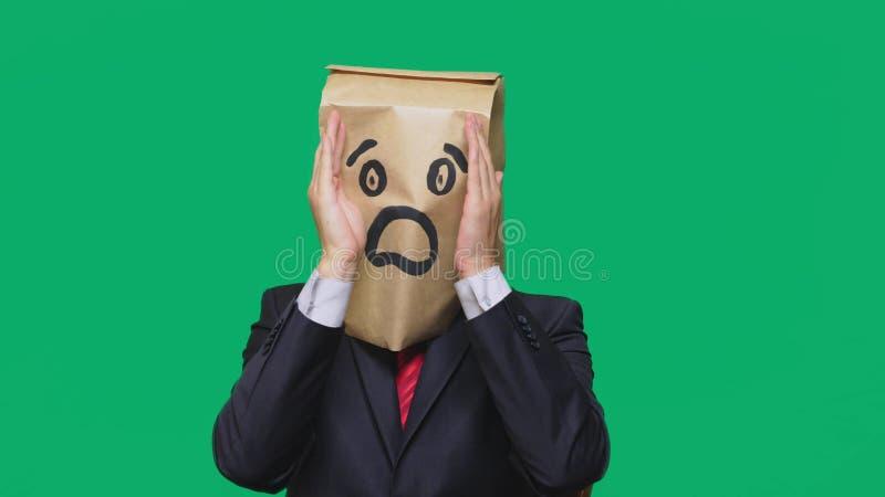 Konzept von Gefühlen, Gesten ein Mann mit Papiertüten auf seinem Kopf, mit einem gemalten Emoticon, Furcht lizenzfreies stockfoto
