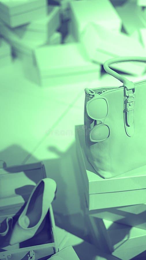 Konzept von modischen weiblichen Zusätzen bauschen sich, Sonnenbrille, Schuhe auf leeren Kästen und grüner Pastellhintergrund stockbild