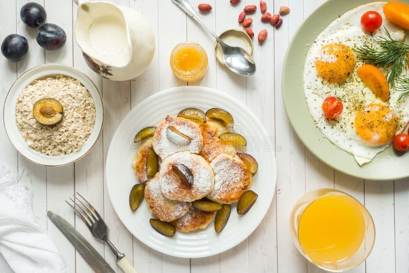 Konzept von Spiegeleiern des Frühstücks, von Hüttenkäsepfannkuchen, von Pflaumen und von Hafermehl mit Milch, Orangensaft auf dem stockbild