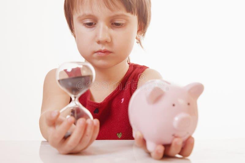 Konzept: Zeit ist Geld Humorvolles Porträt des netten kleinen Geschäftskindermädchens, das eine Sanduhr und -Sparschwein hält Hor lizenzfreies stockfoto