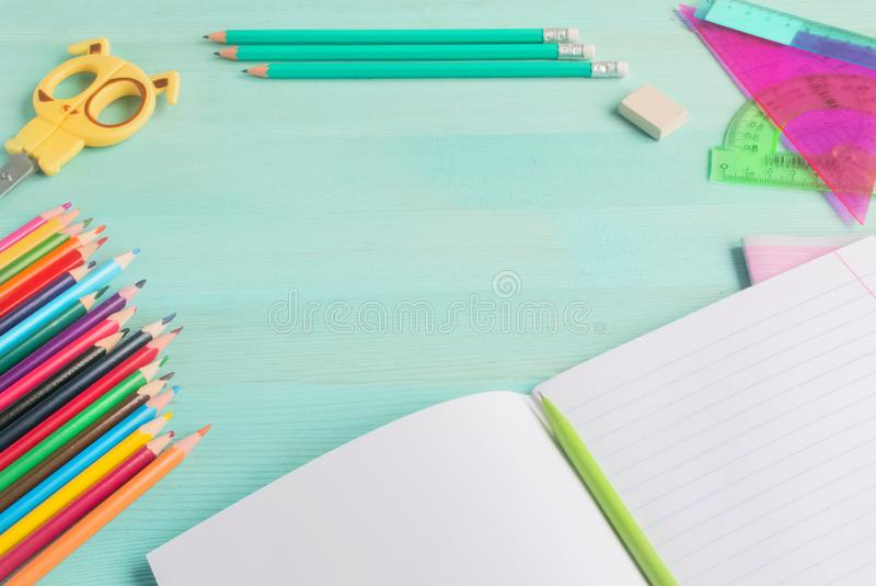 Konzept zur?ck zu Schule Schulzusätze, farbige Bleistifte, Stift mit leerem Notizbuch auf blauem hölzernem Hintergrund lizenzfreie stockbilder