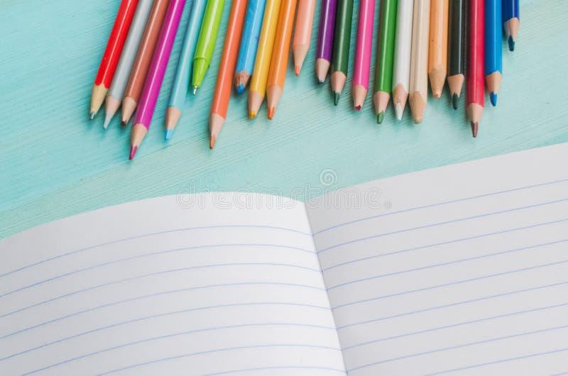 Konzept zur?ck zu Schule Schulzusätze, farbige Bleistifte, Stift mit leerem Notizbuch auf blauem hölzernem Hintergrund stockfoto