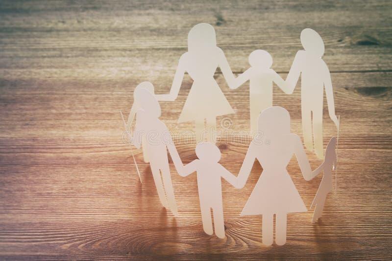 Konzeptbild des Familienpapierketten-Ausschnitthändchenhaltens, über Holztisch stockbilder