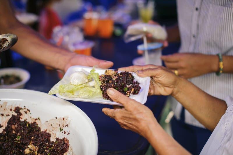 Konzepte der Armut in der asiatischen Gesellschaft: Freiwillig-Anteil-Nahrung zu den Armen, zum des Hungers zu entlasten stockbild