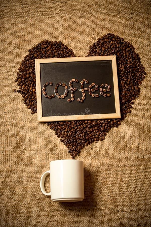Konzeptfoto der Liebe zum Kaffee mit Bohnen, Becher und Tafel stockfotos