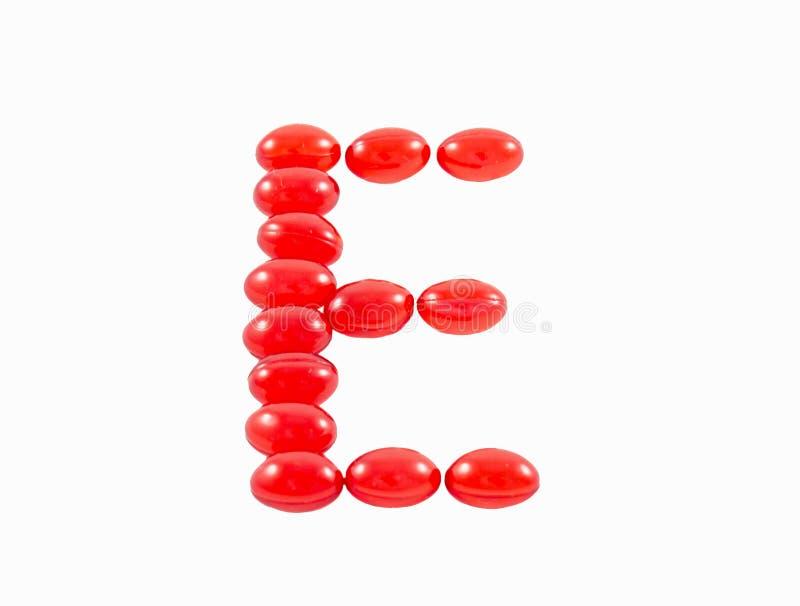 Konzeption des Vitamins e gemacht von den roten Pillen in Form e-Buchstaben lokalisiert lizenzfreies stockbild