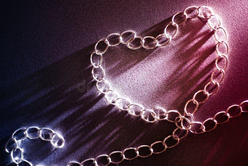 Konzeptliebe und -menschliche Beziehungen Form des Herzens gemacht von der Eisenkette blaue und rote Steigungen am Hintergrund Va lizenzfreie stockbilder