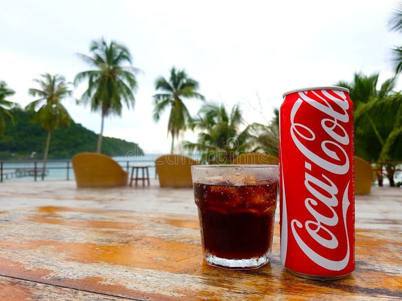 Kood ö, Thailand, 8 Juni 2017: Cocacola kan och i exponeringsglasdrinken för det varma vädret och strandbakgrunden royaltyfri bild