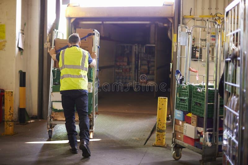 Kooi van het mensen de duwende broodje in een vrachtwagen bij een pakhuis, achtermening royalty-vrije stock foto's