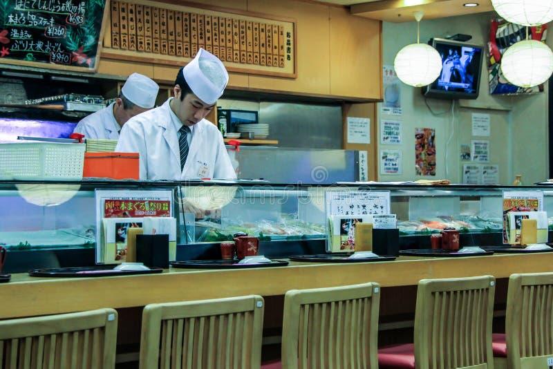 Kooktoestellen in de sushibar Een mensen kokende sushi en broodjes Nationaal voedsel van Japan stock afbeeldingen